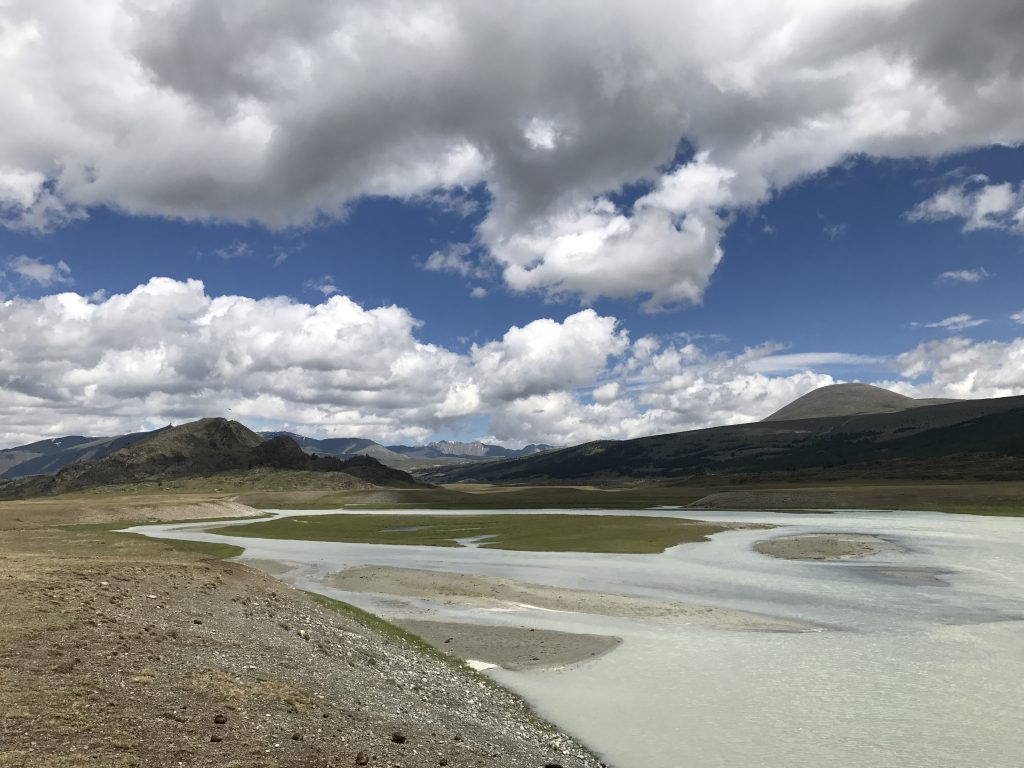 blue skies with clouds above a barren, half dried river